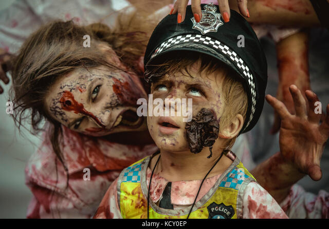 Sitges, Spain. 7th Oct, 2017. A young boy made-up as zombie COP is besieged by other 'zombies' at the beginning - Stock Image
