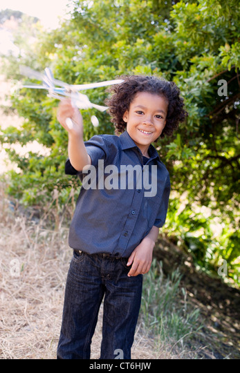 A small boy is playing with a toy airplane. - Stock Image