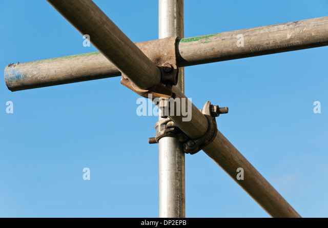 Close up of joint in scaffold poles against a blue sky. - Stock Image