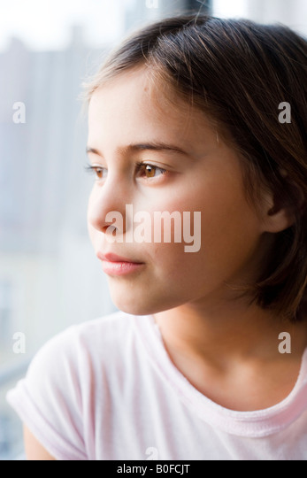 Girl looking out of window - Stock Image