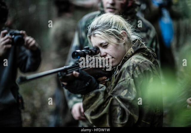 Groups of people dressed up in combat camouflage  uniforms and carrying paint-ball guns hunting zombies in the woods - Stock Image