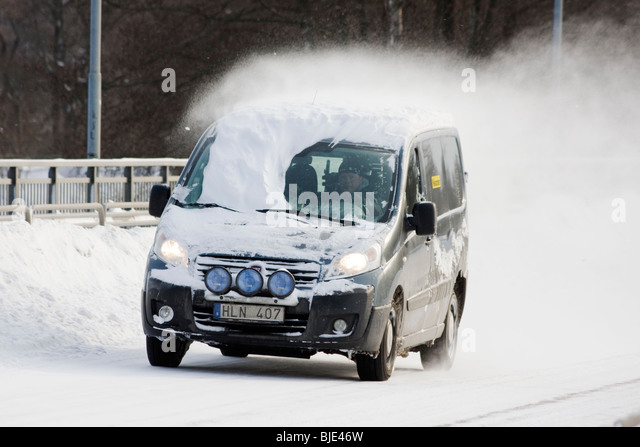 Man driving a minivan with snow on the windshield - Stock Image