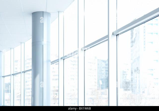 Image of big windows passing daylight inside office building - Stock Image