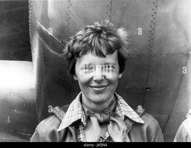 Amelia Earhart standing under nose of her Lockheed Model 10-E Electra. - Stock Image