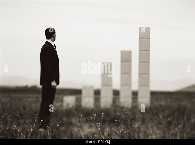 Man out on field with stacked up boxes forming a graph. - Stock-Bilder