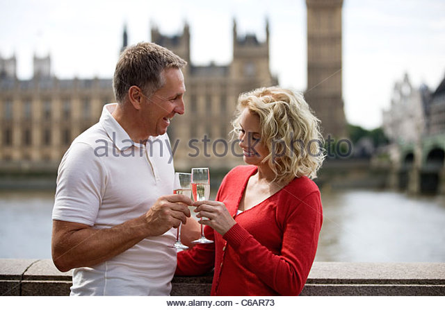 A middle-aged couple in front of the Houses of Parliament, toasting with champagne - Stock Image