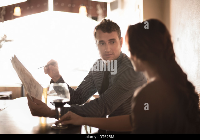 Business partners looking at contract in a wine bar - Stock-Bilder