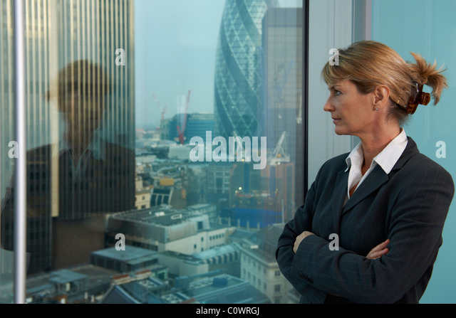 Senior business woman looking out of window with city of London in background - Stock Image