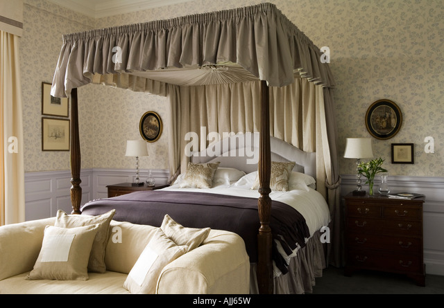 Fourposter bed and sofa in bedroom with patterned purple wall paper in 17th century Irish castle - Stock Image