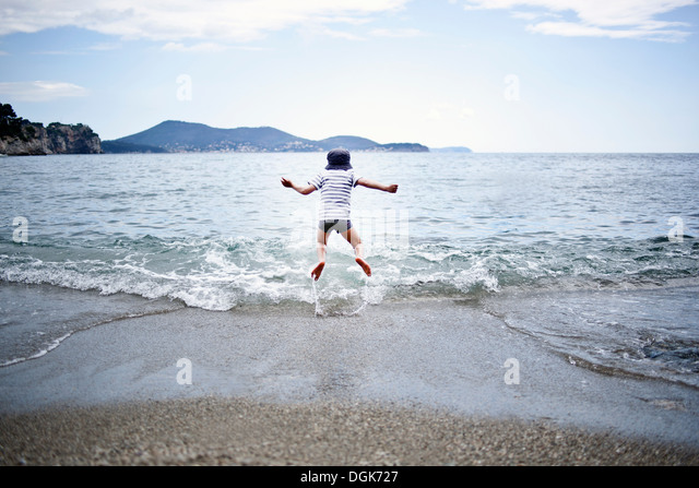 Little boy jumping into the sea - Stock Image