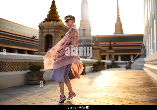 Beautiful girl is walking and exploring temple. Sunset on the background. - Stock-Bilder