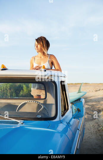 Young female surfer looking from back of pick up truck, Leucadia, California, USA - Stock Image