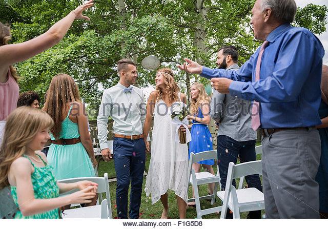 Guests throwing confetti over bride groom backyard wedding - Stock Image