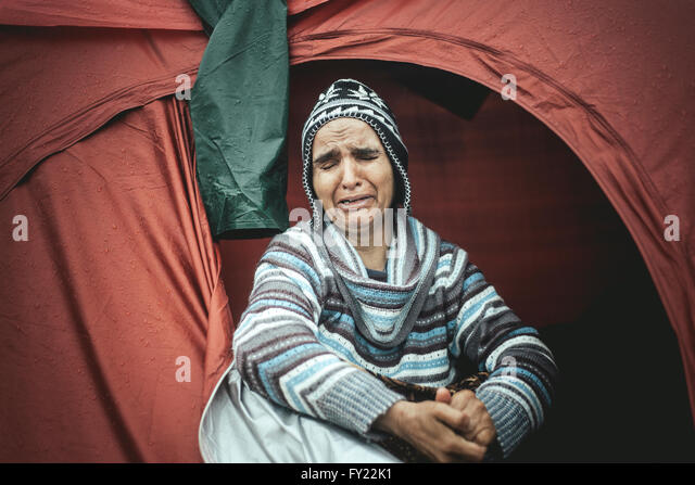 Desperate woman from Afghanistan weeping in her tent, refugee camp Idomeni, border with Macedonia, Greece - Stock Image
