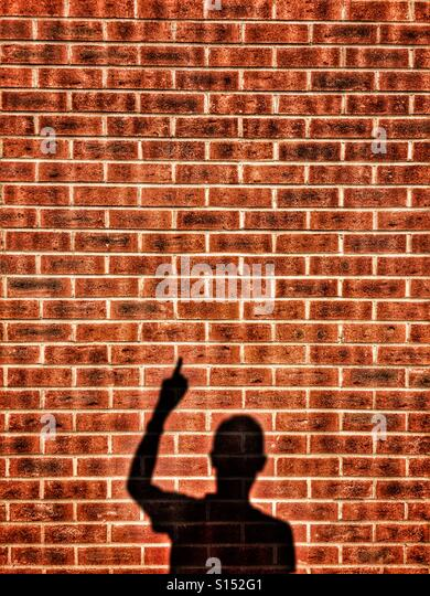 Shadow of man pointing on a brick wall - Stock-Bilder