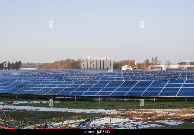 Solar cell park in the winter with snow and blue sky and an industrial building in the background - Stock Image