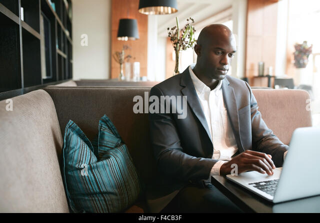 Image of young man sitting at cafe working on laptop. African businessman at coffee shop surfing internet on laptop. - Stock-Bilder