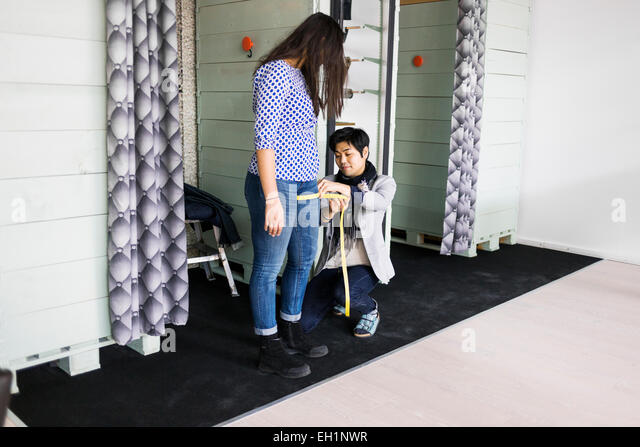 Fashion designer measuring woman's thigh in jeans factory - Stock Image