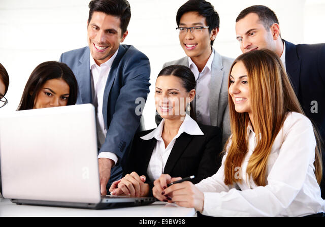 Smiling businesspeople working on the laptop together - Stock Image