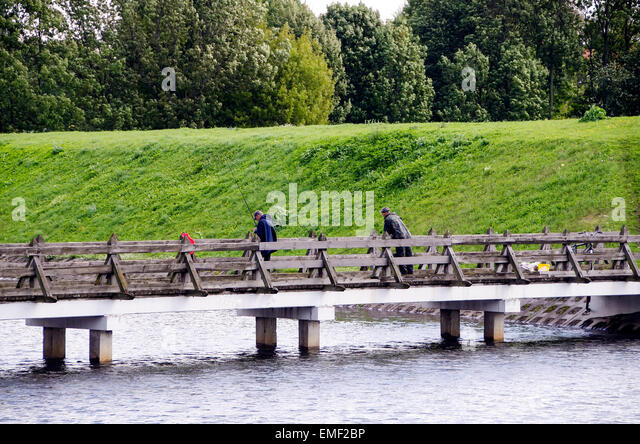 Klaipeda Lithuania men fishing from bridge crossing moat beside old earthen fort rampart defense walls built in - Stock Image