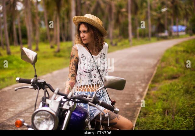 Edgy tattooed woman sitting on a motorbike - Stock Image