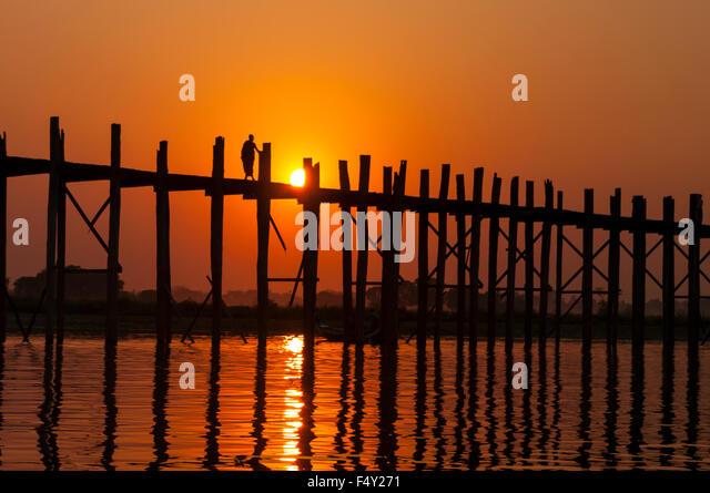 Lone Buddhist monk crossing U Bein Bridge, a 1.2 km long teakwood bridge, at sunset. Amarapura, Mandalay Region, - Stock-Bilder