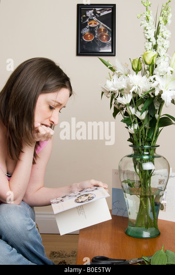 Recently bereaved young woman  viewing a sympathy card with floweres - Stock Image