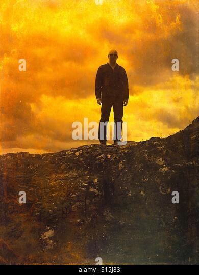 Looking up at the man on the rocks. - Stock-Bilder