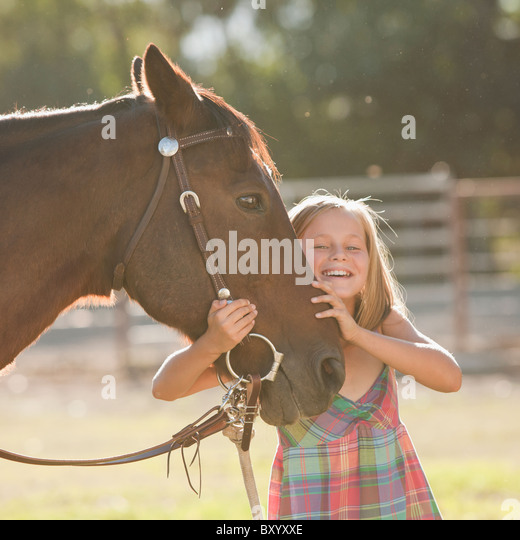 Portrait of smiling cowgirl with horse in ranch - Stock-Bilder