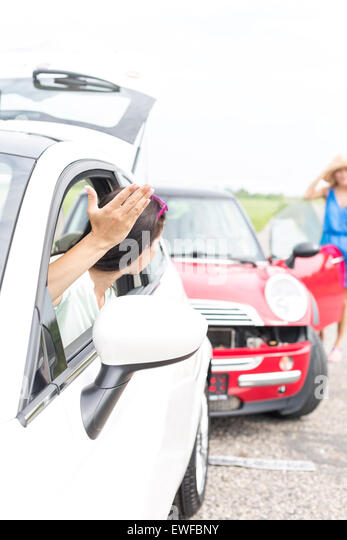 Angry woman gesturing while talking to female crashing car on road - Stock Image