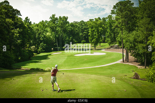 Elevated view of young male golfer teeing off on golf course, Apex, North Carolina, USA - Stock Image