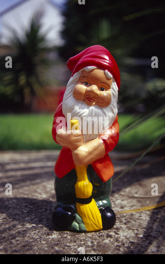 Garden gnome with a sweeping brush in a suburban garden on a sunny Summer day - Stock Image