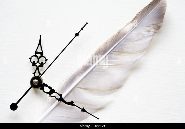 Art concept. Closeup of quill near clock face on paper background - Stock Image
