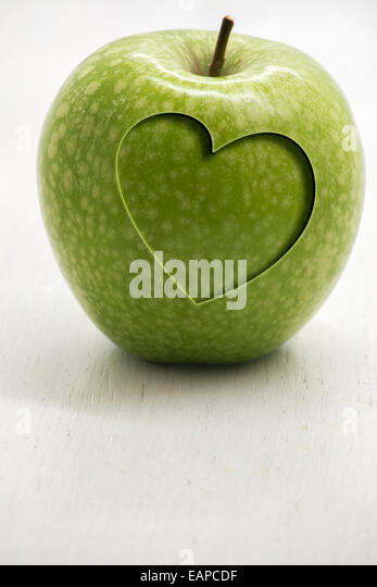 Green apple with carved heart, conceptual health and wellness - Stock-Bilder