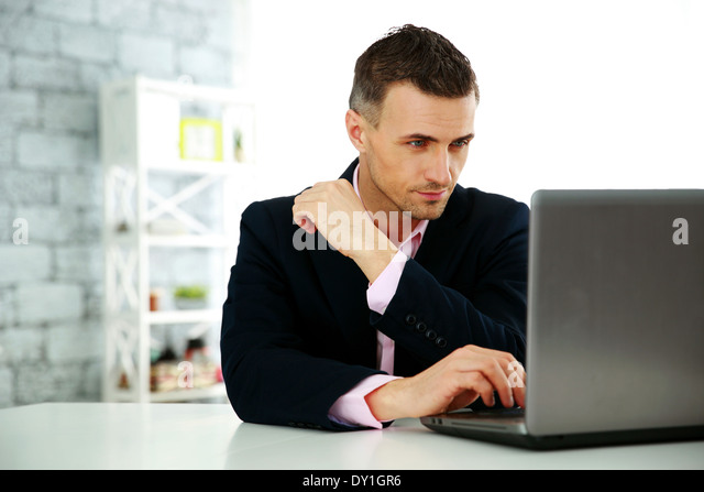 Confident businessman working on a laptop at office - Stock Image