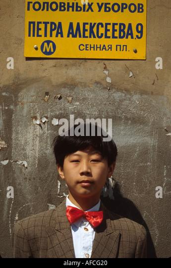 Russia former Soviet Union St. Petersburg young resident of Asian descent near Sennaya Ploshchad Metro Station - Stock Image