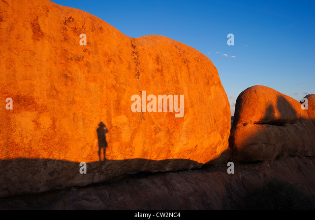 Shadow of a man against Spizkoppe rock formation.Namib Desert.Namibia - Stock Image