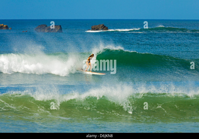 Girl surfing at Playa Guiones beach, Nosara, Nicoya Peninsula, Guanacaste Province, Costa Rica, Central America - Stock Image