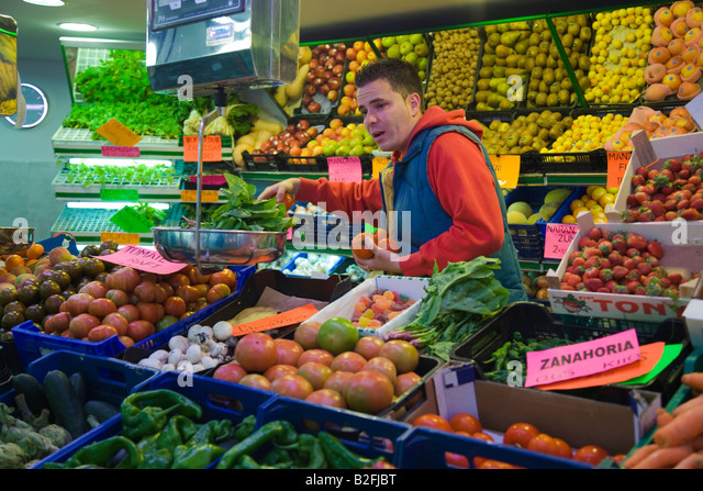 SPAIN Salamanca Man select fresh produce for customer at fruit and vegetable booth in indoor market - Stock Image