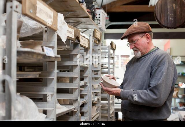 Potter wearing flat cap in storage room quality checking unfinished clay pots - Stock Image