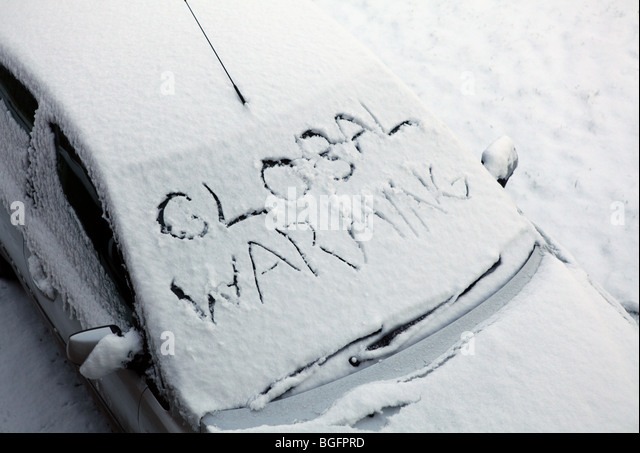 A snow covered car with the words Global Warming written in the snow in the big freeze of 2010 - Stock Image