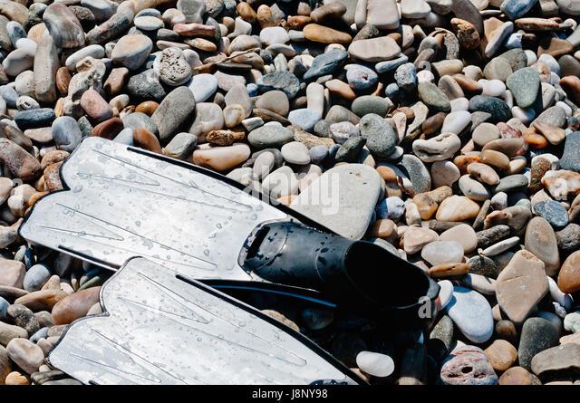 Swim fins on pebbles - Stock-Bilder