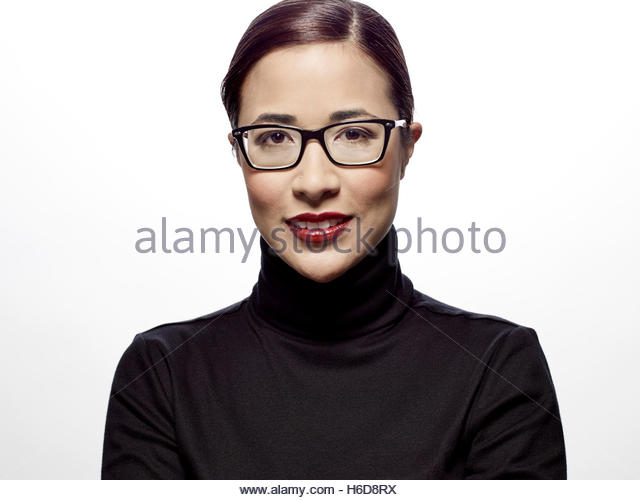 young businesswoman smiling looking at camera in studio with white background - Stock Image