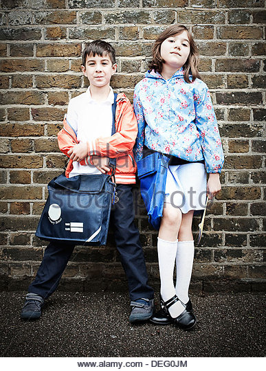 Boy and girl standing in front of brick wall with school bags - Stock-Bilder