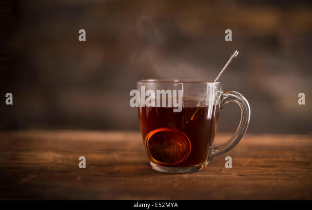 Clear glass of steaming hot tea with infuser on wooden, rustic suface. - Stock Image