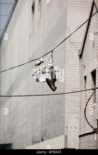 Shoes hanging by their laces on a wire in the city - Stock Image