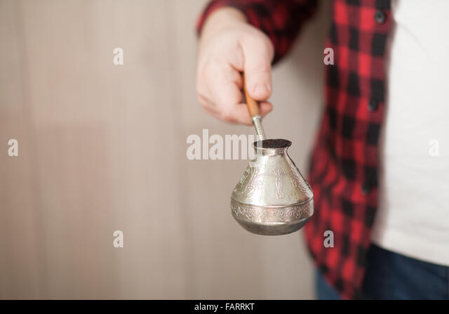 Man holding a cezve with homemade coffee - Stock Image
