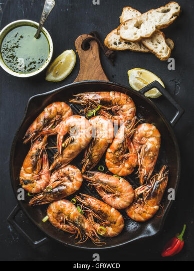Roasted tiger prawns in iron grilling pan on wooden board with fresh leek, lemon slices, pepper, bread and pesto - Stock Image