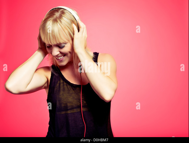 Attractive young woman looking down while enjoying the music from her mp3 player - Stock Image