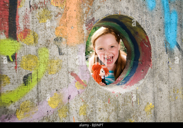 portrait of laughing girl looking through hole in wall on playground - Stock Image